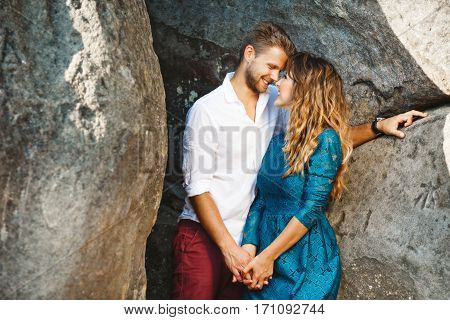 Nice couple standing together very close to each other near rocks, outdoor. Beloved holding hands of each other, looking at each other and smiling. Profile. Girl wearing blue dress and man wearing white shirt and claret trousers, he has stylish haircut