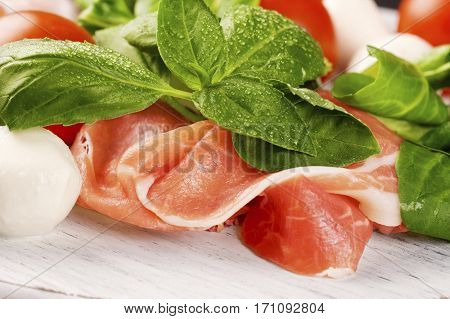 Prosciutto Smoked Pork Ham Rashers with tomato and mozzarella on the wooden table
