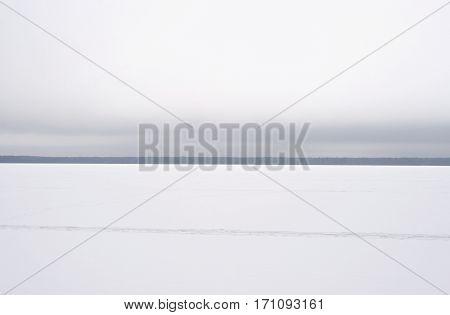 Frozen lake at cloud winter day in Leningrad region Russia.