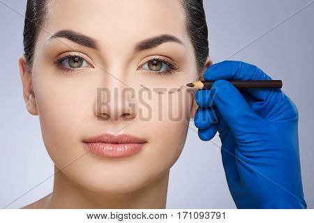 Plastic surgeon drawing dashed line under eye of girl. Hand in blue glove holding pencil. Plastic surgery, beauty portrait, closeup
