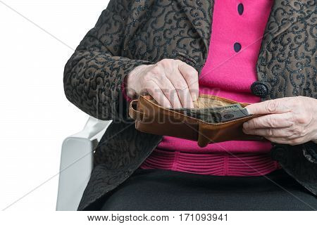 Hands of an old woman holding a purse with dollars sticking out of it, close-up