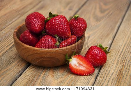 Ripe red strawberries in a wooden plate on a wooden background