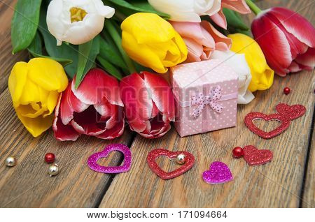 A bouquet of colored tulips with gift box on a wooden background