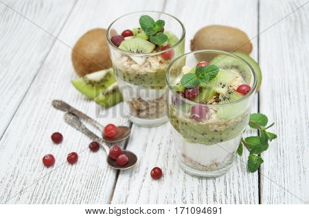 Healthy breakfast with kiwi yogurt muesli and cranberry. Layered cream dessert