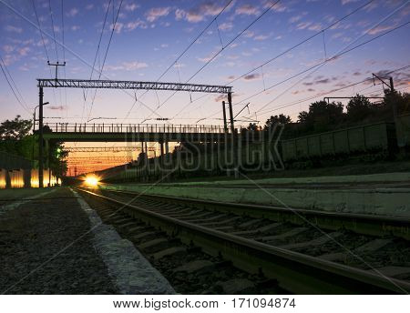 The train at sunset approaches the station