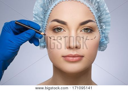 Plastic surgeon drawing dashed lines under eyes of girl. Hand in blue glove holding pencil. Beautiful girl in protective cap. Plastic surgery, beauty portrait