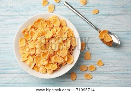 Bowl with cornflakes on white wooden background