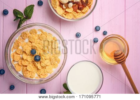 Tasty cornflakes with blueberries,nuts and raisins on pink background