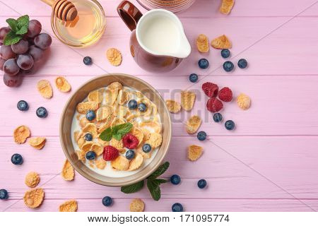 Tasty cornflakes with raspberries and blueberries on pink background