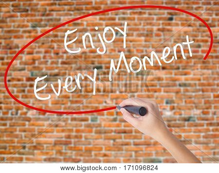 Woman Hand Writing Enjoy Every Moment With Black Marker On Visual Screen.