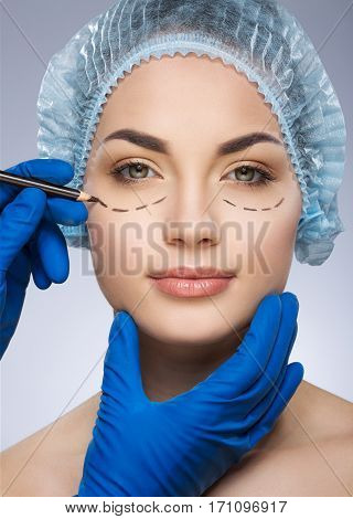Plastic surgeon drawing dashed lines under eyes of girl. Hands in blue glove holding pencil and face. Smiling girl in protective cap. Plastic surgery, beauty portrait, half face