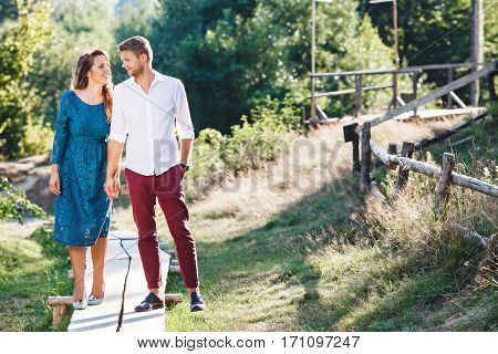 Nice couple walking together, outdoor, in the countryside. Beloved looking at each other, holding hands of each other and smiling. Woman wearing blue dress and light blue shoes and man wearing white shirt, claret trousers and black shoes. Full body