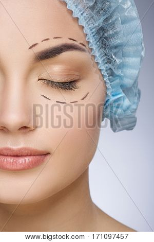 Dashed lines around eyes of girl. Beautiful girl with closed eyes in protective cap. Plastic surgery, beauty portrait, half face, closeup