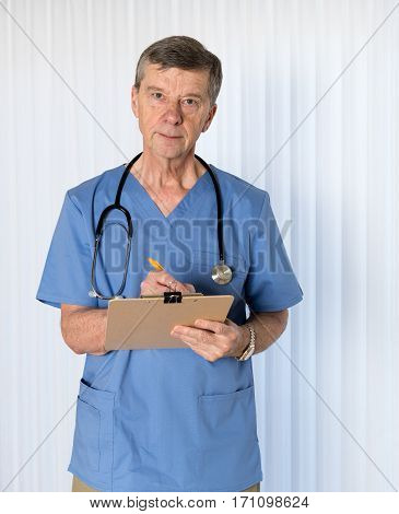 Senior male caucasian doctor with stethoscope in medical scrubs and confidently facing the camera in portrait
