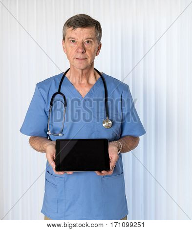 Senior male caucasian doctor with stethoscope in medical scrubs looking up and holding electronic tablet for message