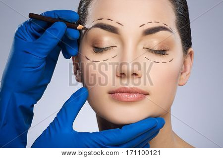 Plastic surgeon drawing dashed lines around closed eyes of girl, above her eyebrow. Hands in blue glove holding pencil and face. Plastic surgery, beauty portrait, closeup