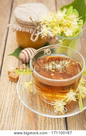 A cup of herbal linden tea with flowers and honey on a wooden background