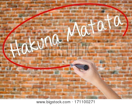 "Woman Hand Writing Hakuna Matata (swahili Phrase; It Means ""no Worries"") With Black Marker"