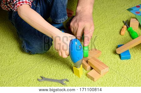 the father teaches the child to use the tool