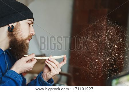 Worker with a beard wearing blue jeans suit and black hat holding wooden spoon and blowing dust, woodcarving, portrait, copy space, woodworking.