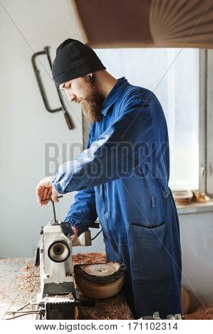 Man with a beard wearing blue jeans suit and black hat working near table, woodcarving instruments on table, big window at background, portrait, woodworking.