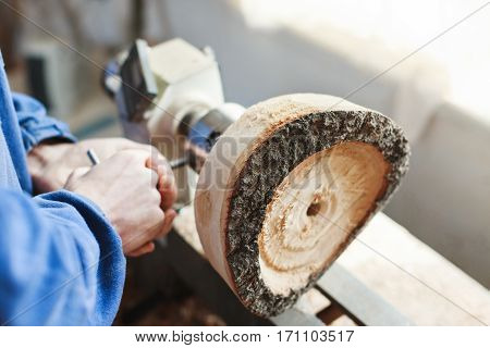 Man's hands in  blue jeans suit working with woodcarving machine and wood, close up, copy space.