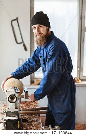 Worker with a beard wearing blue jeans suit and black hat working near table, woodcarving instruments on table, big window at background, looking at camera.