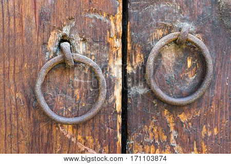 Two rusty iron ring door knobs over an old wooden weathered door