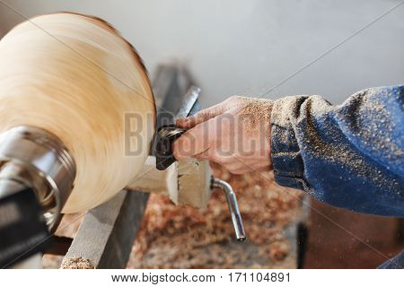 Worker's hands in  blue jeans suit working with woodcarving machine and wood, shavings on table, close up, woodworking.