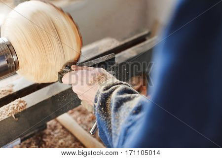 Man's hands in  blue jeans suit working with woodcarving machine and wood, shavings on table, close up, copy space.