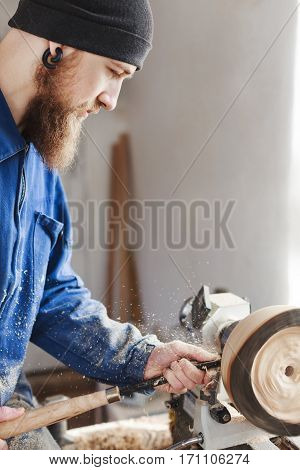 Man with a beard wearing blue jeans suit and black hat working with woodcarving machine, white wall at background, portrait, copy space.