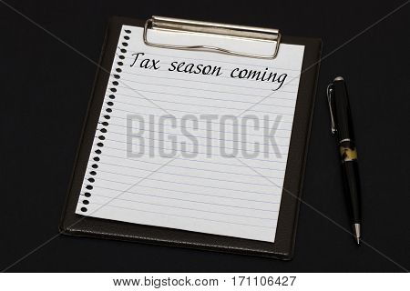 Top View Of Clipboard And White Sheet Written With Tax Season Coming On Black Background. Business C