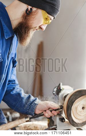 Worker with a beard wearing blue jeans suit, black hat and glasses working with woodcarving machine, white wall at background, portrait, woodworking. poster