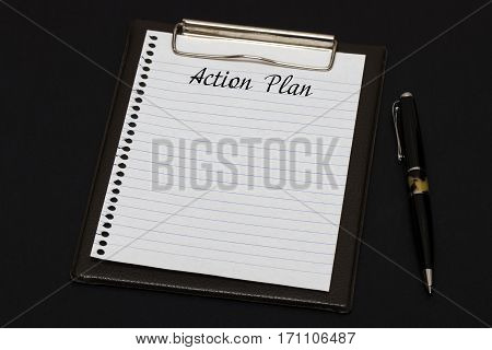 Top View Of Clipboard And White Sheet Written With Action Plan On Black Background. Business Concept