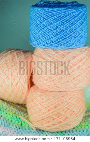 Three Balls Of Pink Yarn And Blue Ball Of Yarn.
