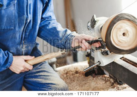 Man in  blue jeans suit working with woodcarving machine, instruments and wood, shavings on table, close up, woodworking.