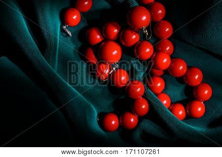 Red coral necklace and earrings at the dark green velvet background on the right side of the frame.