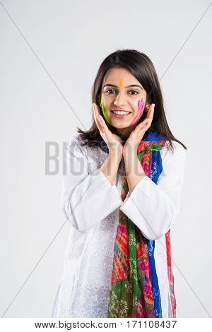 Indian smart young girl with face coloured with gulal touching face with both hands, looking at camera with a pleasant look, isolated over white background