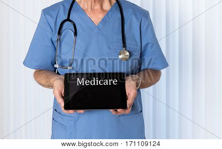 Senior male caucasian doctor with stethoscope in medical scrubs looking up and holding electronic tablet for Medicare message