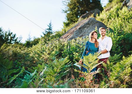 Nice couple standing together among fern and trees, outdoor, in the countryside. Girl looking at her boyfriend and he looking aside. Beloved embracing each other by one hand and smiling. Woman wearing blue dress and man wearing white shirt, claret trouser