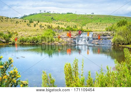 HORTON PLAINS PARK SRI LANKA - NOVEMBER 30 2016: The buddhist monks rest and play in small waterfall on November 30 in Horton Plains Park