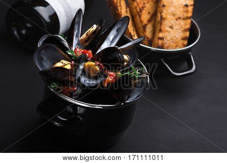 Casserole With Mussels. A Bottle Of Wine And A Baguette, Black Background.