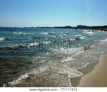 Beach holidays vacation background. sandy beach by the blue ocean. golden sand on the shores of the ocean. Ocean waves breaking on the rocks on the shore.