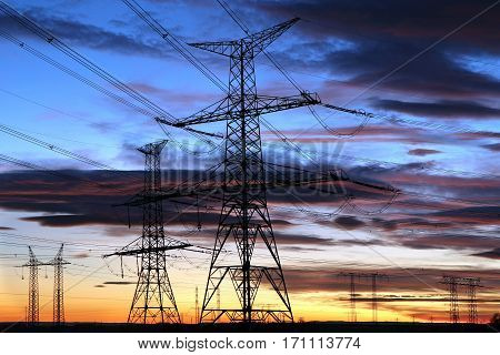 dark Silhouette of electricity pylons during sunset