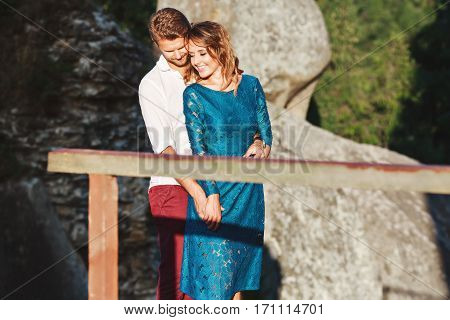 Nice couple standing together near rock and wooden bridge, outdoor, in the countryside. Girl has closed eyes, head turned aside and smiling and man holding her hand and embracing her. He looking down and smiling too. Woman wearing blue dress and man weari