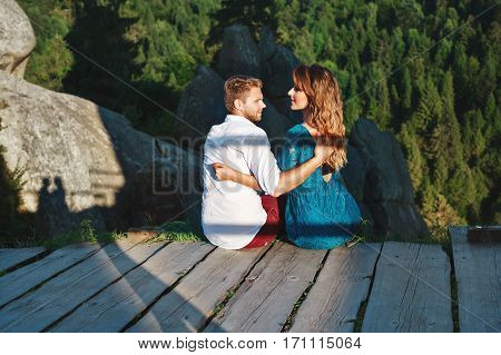 Cute couple sitting on a wooden path near rocks. Looking at each other. Beloved embracing each other by one hand. Woman wearing blue dress and man wearing white shirt and claret trousers. Profile