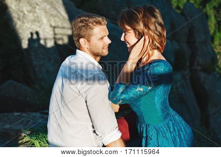 Cute couple sitting near rocks in shadow. Nice beloved looking at each other. Girl holding her hair by one hand. Woman wearing blue dress and man wearing white shirt and claret trousers. Profile