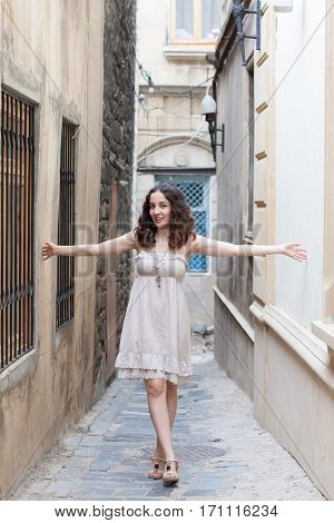 Young curly girl wearing romantic biege dress with lace on narrow streets of old downtown of Baku touching walls with her hands