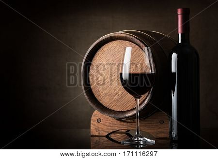 Red wine near wooden barrel on a brown background