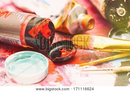Painter workplace with tubes of multicolor oil paint and paintbrushes on painted paper close up with selective focus.
